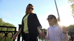 Mother and daughter walking in the Park holding hands - stock footage