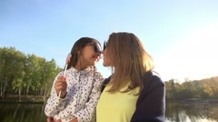 Mother and daughter hugging and looking at camera Stock Footage