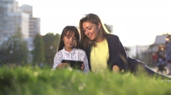 Mother and daughter 8 years old and playing on the tablet resting in the city Stock Footage