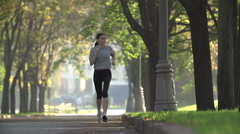 Beautiful young model girl training runs in the Park, slow motion Stock Footage