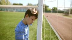 Teen boy upset defeat by knocking goal goal post net stadium turf Stock Footage