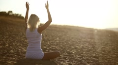 Woman in white sitting on sand meditation healthy lifestyle sunset the sun goes Stock Footage