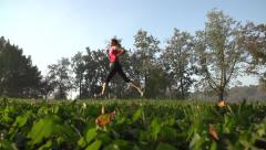 Young fitness woman having an exercise run in a park, slow motion Stock Footage