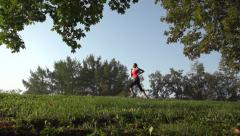 Girl runs through Park in the morning,slow motion,dolly shot Stock Footage