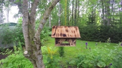 Wooden birdhouse, swinging in the wind, at a garden - stock footage