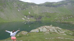 Little girl running near the lake on Transfagarasan Stock Footage