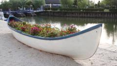 A rowboat filled with an assortment of flowers on the Golovita Lake shore Stock Footage