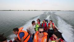 Tourists take a tour on lake aboard a high speed boat - stock footage