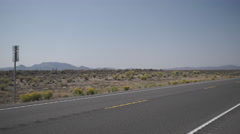 Car Drives Along A Road in the Desert Stock Footage