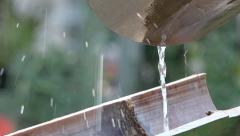 Water flowing from hanging half bamboo, drops falling - Close up 1 Stock Footage