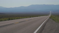 Distant Vehicle Drives Along A Road in the Desert Stock Footage