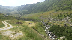 Tourists walking near a river in Transfagarasan's valley Stock Footage