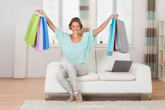 Young Happy Woman Sitting On Sofa With Multi-colored Shopping Bags At Home Stock Photos