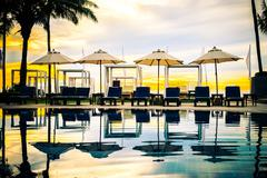 Silhouette palm tree with umbrella chair pool in luxury hotel resort at sunri Stock Photos