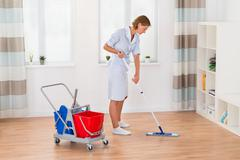 Young Female Housekeeper Cleaning Floor With Mop In House - stock photo