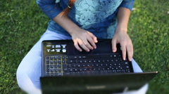 Young girl using laptop in park Stock Footage