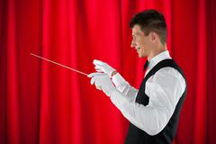 Male Orchestra Conductor Holding Baton Over Red Curtain - stock photo