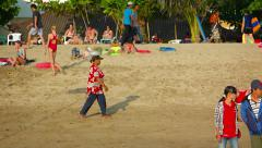 Local fruit vendor strolling along a popular tourist beach in Kuta, Bali Stock Footage