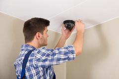 Young Male Technician Installing Surveillance Camera On Ceiling - stock photo