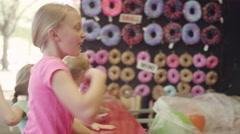 Three little girls playing a bean bag toss at a fair - stock footage