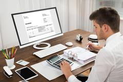 Male Accountant Calculating Tax In Front Of Computer At Desk Stock Photos