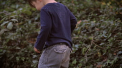 A little cute boy with baggy pants walking in grass in slow motion Stock Footage