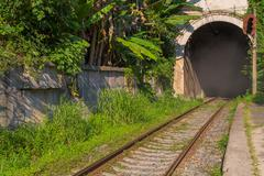Old railroad with the arch of the tunnel - stock photo