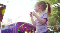Stock Video Footage of A little girl with strawberry blonde hair eating cotton candy and smiling