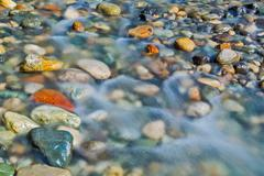 Pebble stones in the river water close up view - stock photo