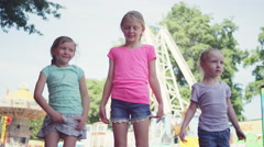 Three little girls at a fair give a group hug and smile at the camera - stock footage