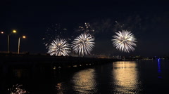 A fireworks display over water marks a big holiday. Stock Footage