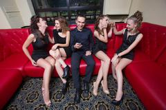 a man holding a cell phone. next four girls - stock photo