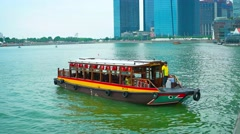 Tour boat idling in Marina Bay under the highrise architecture in Singapore Stock Footage