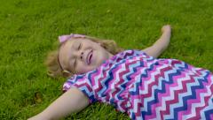 Little Girl Pretends To Make Snow Angel, Picks Grass, Sprinkles It In Air, Waves Stock Footage