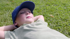 Little Boy Relaxes In Grass, He Blows A Kiss At Someone Off-Screen And Smiles Stock Footage