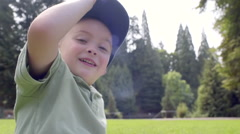 Silly Boy Plays With Hat, Puts It Over Lens, Then Puts It On His Head, Smiles Stock Footage