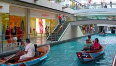 Sampan rides along the canal inside the Shoppes at Marina Bay Sands Stock Footage