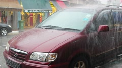Heavy rain and roof runoff pouring over a parked car on an urban street Stock Footage