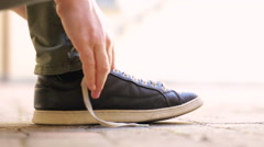 Male man lacing up shoes and walking away Stock Footage