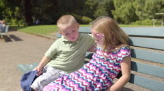 Cute Little Kids Sit On Bench Together, Boy Put His Arm Around Girl Stock Footage