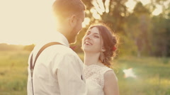 Young beautiful couple laughing bride and groom in the park at sunset the sun - stock footage