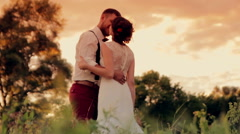 Young beautiful couple bride and groom gently embracing  and kissing in  the Stock Footage