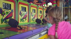 Stock Video Footage of Three little girls step up to play a carnival game together