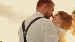 Young beautiful couple bride and groom gently embracing  and kissing in the park Stock Footage