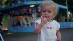 A cute toddler licking cotton candy off of her fingers at a fair - stock footage