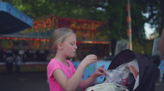 Stock Video Footage of A young girl getting cotton candy out of a bag and sharing it