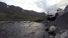 Action camera low angle view at the suv car driving across the river on stones Stock Footage