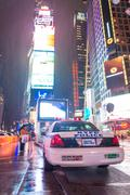 NEW YORK CITY - JUNE 13, 2013: Rainy night with tourists in Times Square. Tim - stock photo