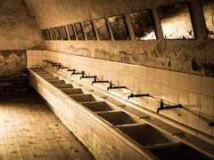 Old mass bathroom in prison - stock photo