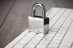 Padlock and white computer keyboard on the wooden office table Stock Photos